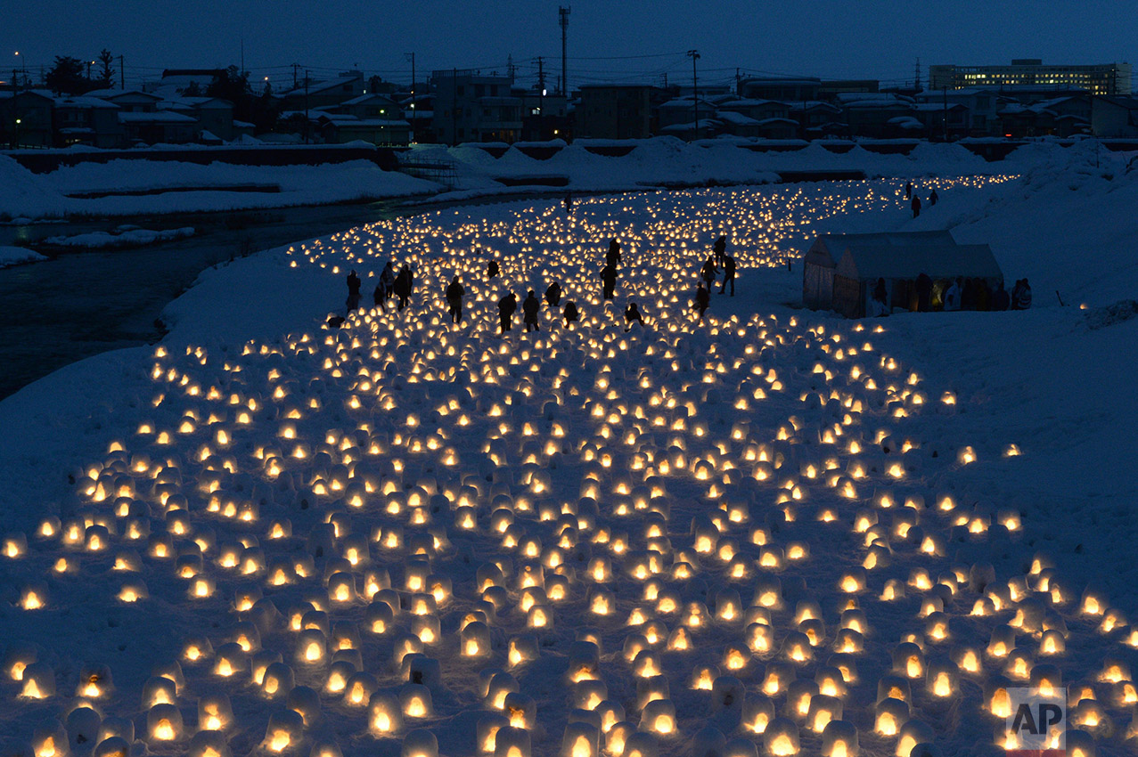 Visitors walk through countless mini kamakura, made by carving out a mound of snow during Yokote Kamakura Snow Festival in a snow country Yokote, Akita Prefecture on Feb. 15, 2017. The candle-lit snow white kamakura create a fantastic spectacle in the dark night. ( The Yomiuri Shimbun via AP Images )